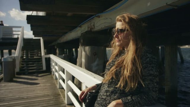 woman on pier with sunglasses