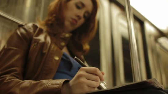 woman writing on train