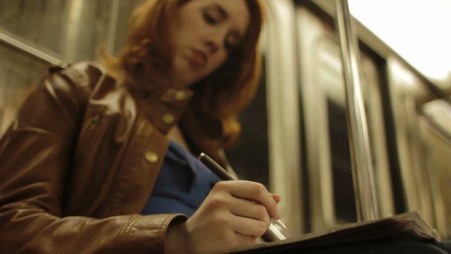 woman writing on train