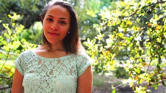 Black woman standing among trees smiling