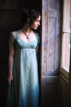 Victorian woman in blue dress looking out the window