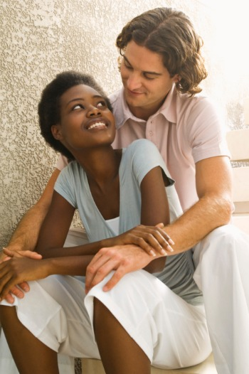 young interracial couple sitting on steps