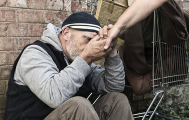 homeless man holding person's hand
