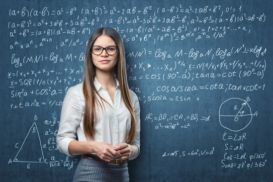 Young businesswoman standing on the background of blackboard with mathematical
