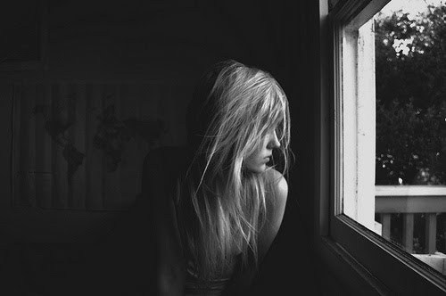 bw of woman looking out window
