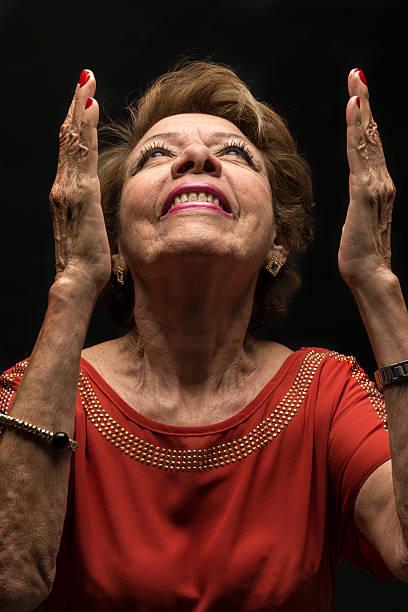 senior woman praying looking up on black background