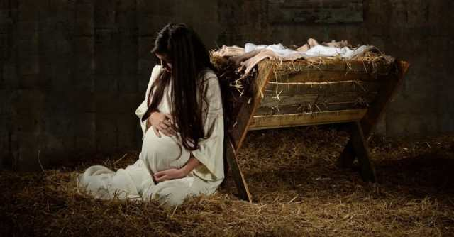 Young pregnant Mary praying leaning on manger on Christmas Eve